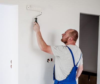 man painting an interior wall in a house