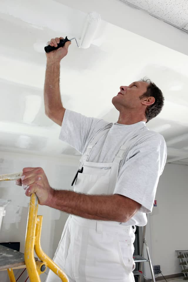 man painting the ceiling on a yellow step ladder
