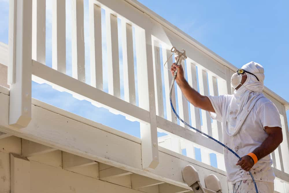 man spray painting the rooftop deck railing white