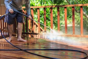man pressure washing a wood deck